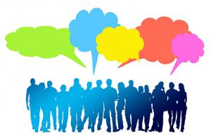 Ryhmä ihmisiä ja vihreä, sininen, keltainen, punainen ja pinkki puhekupla.