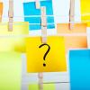 Musta kysymysmerkki keltaisessa post-it lapussa, joka roikuu pyykkipohjalla sinisten ja oranssien post-it lappujen kanssa narulla.
