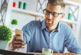 Silmälasipäivinen mies katsoo puhelinta kahvikuppi pöydällä.