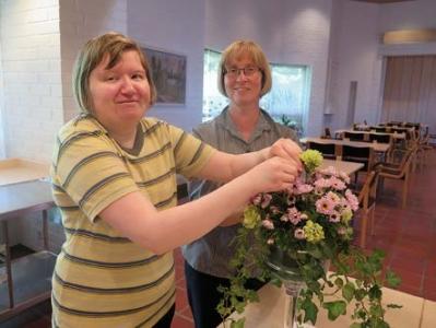 Hanna Pesonen hoitaa kukkia ja emäntä Arja Pikkarainen hymyilee taustalla.