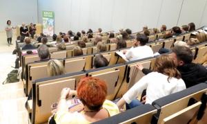 Tapahtuman osallistujat istuskelevat auditoriossa.