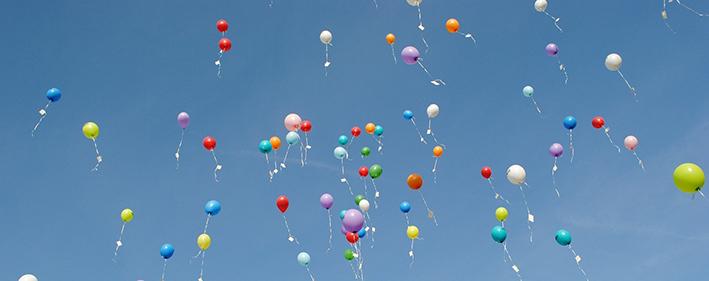 Erivärisiä ilmapalloja taivaalla.