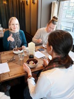 Kolme henkilöä ruokailemassa ja keskustelemassa.