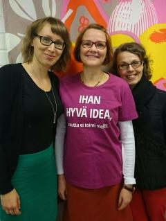 Keski-Suomen Yhteisöjen Tuki ry:n työntekijät oikealta vasemmalle Anne Astikainen, Raili Haaki ja Anu Hätinen hymyilevät kameralle iloisen värisen seinän edessä.