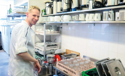Henri Kallio ja puhtaita astioita keittiössä.