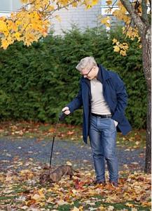 Henri ulkoilee koiransa kanssa syksyisten lehtien peittämällä kadulla.