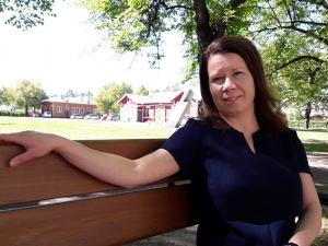 Kehittämispäällikkö Johanna Seppänen istuu puistonpenkillä.