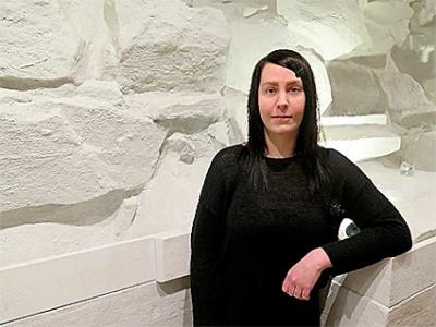 Jonna Kuusisto valkoisen kiviseinän edessä.