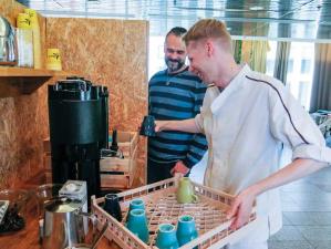 Työvalmentaja Kim Lautamo ja Henri Kallio kahvinkeittimen luona.