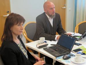 Jaana Pakarinen ja Olavi Sydänmaanlakka pöydän ääreesä, katse oikealle. Pöydällä mm. tietokone.