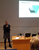Toimitusjohtaja Jaana Pakarinen salin edessä tummissa vaatteissa puhumassa.