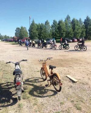 Polkupyöriä ja pyöräilijöitä hiekkatiellä.