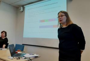 Anne Kallio kertoo tutkimuksesta julkistustilaisuudessa, taustalla diaesitys.