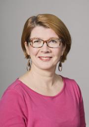 Mervi Ylitalo, jolla silmälasit, vaaleanruskeat hiukset ja fuksianpunainen pusero.