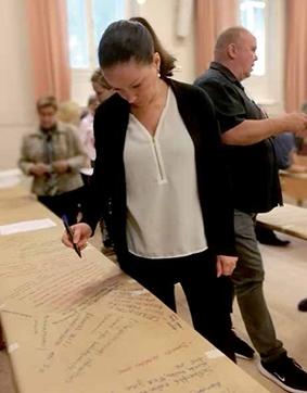 Toiminnanjohtaja Milja Karjalainen kynä kädessä tekemässä merkintään paperille.