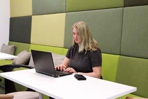 Nora Holmberg istuu tietokoneen äärellä.