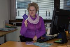 Violettiin puseroon pukeutunut nainen istuu työpöydän ääressä ja katsoo kameraan.