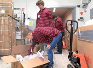 Nuoret miehet töissä Tokmannin varastossa laatikoita purkamassa.