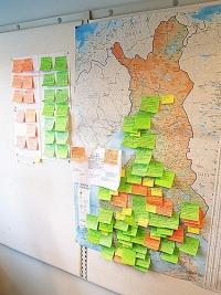 Kartta on Tuulin työhuoneen seinältä, ja auttaa havainnollistamaan hankkeiden määrää eri puolilla Suomea. Vihreät post-it -laput on käynnissä olevia hankkeita ja oranssit päättyneitä.