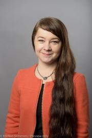 Kati Kaarlejärvi hymyilee kameralle oranssi jakku päällään.