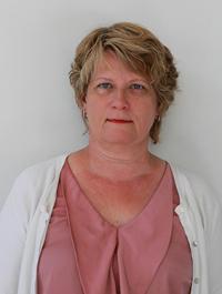 Kirjoittaja Kaija Ray katsoo suoraan kameraan vaaleanpunainen pusero yllään.