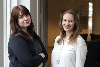 Tuuli ja Hanna hymyilevät iloisesti vierekkäin toimiston aulassa.