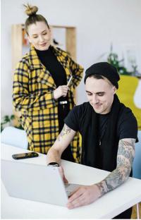 Mies tietokoneella ja nainen katsoo selän takana tekemistä.