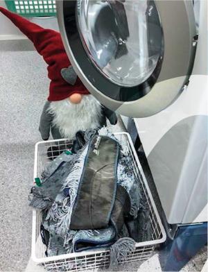 Pesukone, pyykkikori, jossa on lattialiinoja ja punalakkinen valkopartainen tonttu.