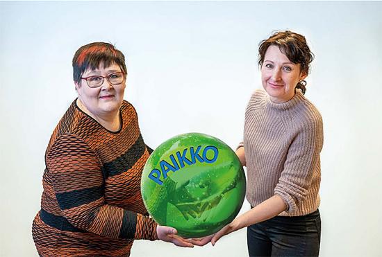 Sanna Uusitalo ja Kaisa Peuha käsissään vihreä suuri pallo, jossa sinisillä kirjaimilla PAIKKO-sana.
