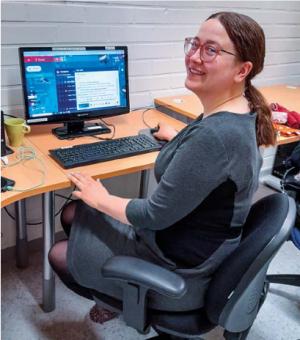 Viivi Kivelä harmaassa mekossa tietokoneen äärellä.