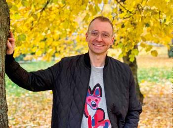 Aki Vuokko nojaa puuhun syksyisessä puistossa.