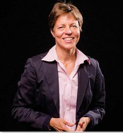 Hymyilevä Sinimaaria Ranki tummassa jakussa vaalenapunaisessa paidassa tumman seinän edessä-