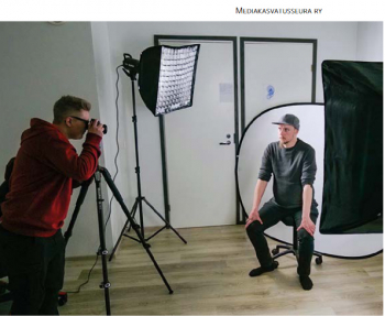 Valokuvaustyöskentelyn harjoittelua mediapajalla, piunapaitainen henkilö kuvaa ja tummapuseroinen henkilö lippalakki päässä istuu tuolilla vallonheittäjien alla kuvattavana.