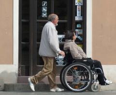 Mies työntää naista pyörätuolissa kadulla.