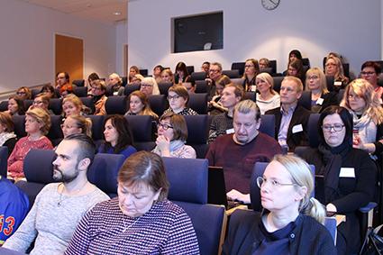 Ihmisiä seminaarissa auditoriossa.