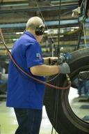 Mies puhdistaa isoa autonrengasta.