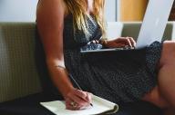 Nainen kirjoittaa vihkoon kynällä, tietokone sylissä.