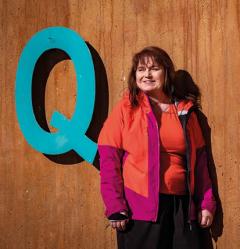 Coltrane seisomassa puuseinän vieressä, seinässä iso Q-kirjain.