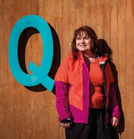 Coltrane Hassinen Q-kirjaimen vierellä puisen seinän edessä punaisessa takissa.