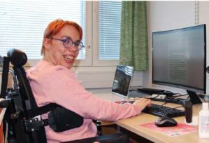 Pyörätuolissa istuva, hymyilevä Essi-Maria tietokoneen ääressä