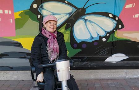 Taustalla suuri sinisävyinen perhonen, edessä hymyilevä nainen sähkömopon kanssa.