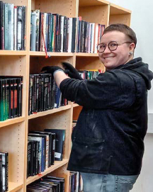 Mikko mustassa hupparissa hymyilee kirjahyllyn luona.