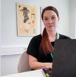 Työvalmentaja Milja Aro seisoo seinällä olevan keltasävyiden julistetaulun edessä tietokoneen äärellä.