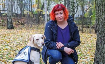 Heini Björk puistossa avustajakoiran kanssa.