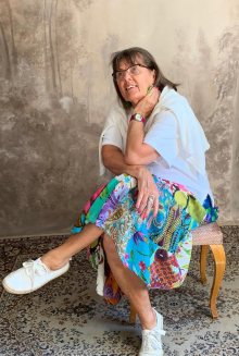 Merja Lind istumassa tuolilla. Silmälasit ja tummat hiukset, värikäs hame.