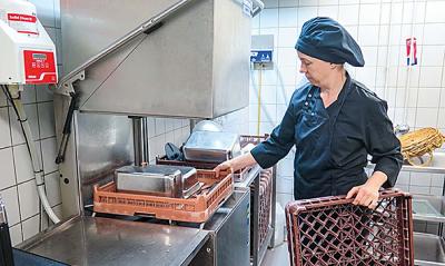 Nainen ravintolan keittiössä tiskikonetta käyttämässä.