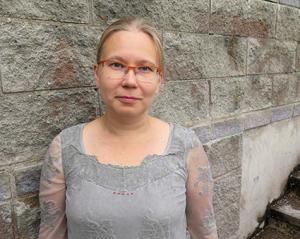 Anne Kallio harmaan kiviseinän edustalla.