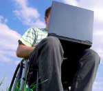 Mies pyörätuolissa, tietokone polvien päällä.
