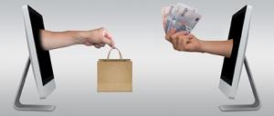 Kuvituskuva, jossa kaksi tietokoneen näyttöä vastakkain. Toisesta tulee ulos käsi ja laukku, toisesta käsi jossa rahaa.