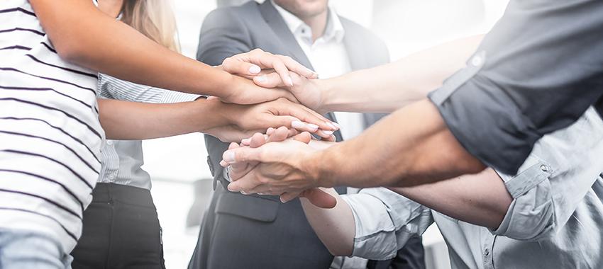 Neljä ihmistä kädet päällekkäin.